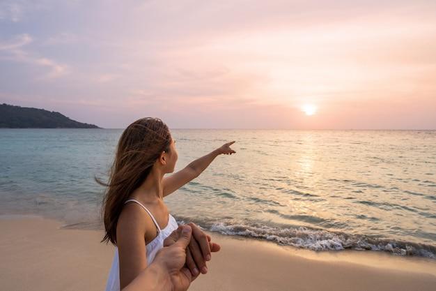 Jonge vrouwenreiziger die man hand houden en mooie zonsondergang op het strand, paar op vakantie in de zomerconcept kijken Premium Foto