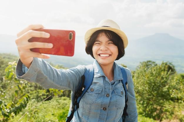 Jonge vrouwenreiziger die selfie met bergmening nemen Premium Foto