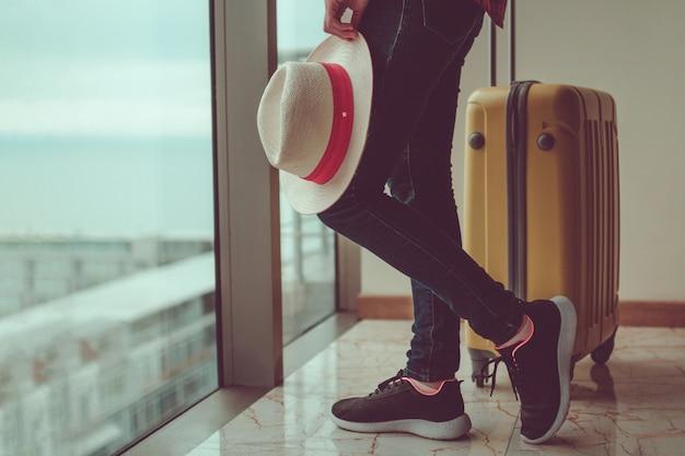 Jonge vrouwenreiziger in vrijetijdskleding met een gele koffer Premium Foto