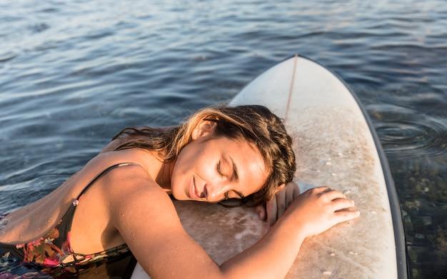 Jonge vrouwenslaap op surfplank Gratis Foto