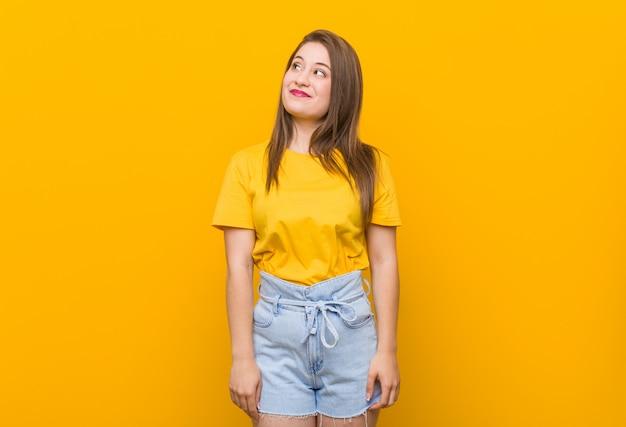 Jonge vrouwentiener die een geel overhemd draagt dat van doelstellingen droomt te bereiken Premium Foto