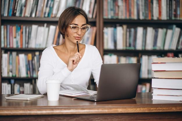 Jonge vrouwenzitting bij de bibliotheek die boeken en computer met behulp van Gratis Foto
