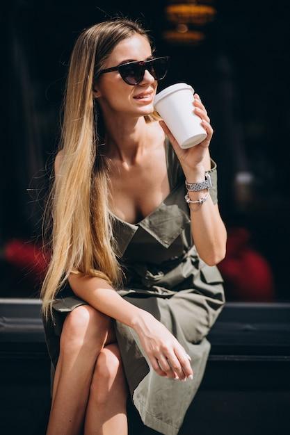 Jonge vrouwenzitting buiten koffie het drinken koffie Gratis Foto