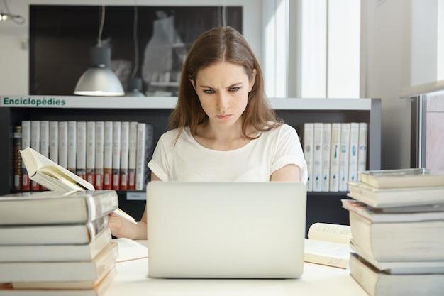 Jonge vrouwenzitting in bibliotheek met laptop Gratis Foto