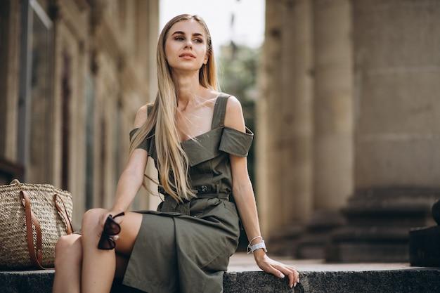 Jonge vrouwenzitting op de treden van een oud bvgebouw Gratis Foto