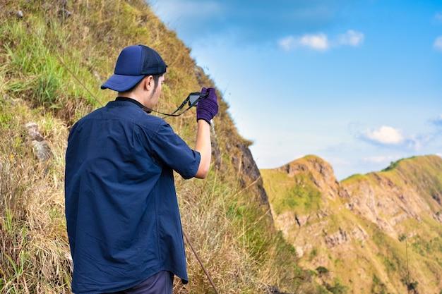 Jonge wandelaar die een fotografie neemt langs weg van het terkking. fotograaf die foto neemt bij bergpiek. Premium Foto