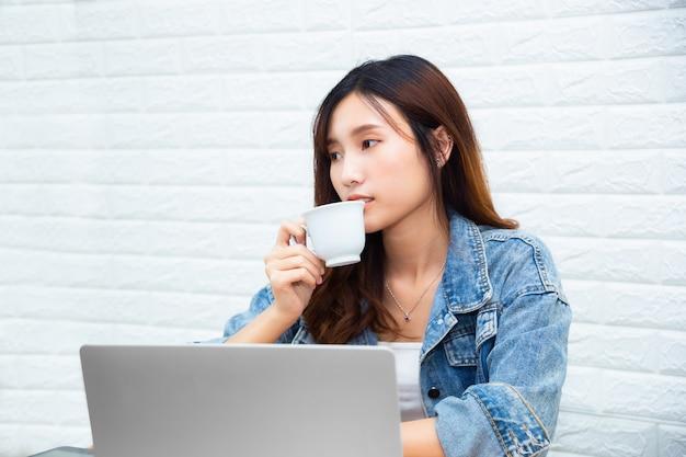 Jonge werkende vrouw het drinken koffie op kantoor Gratis Foto