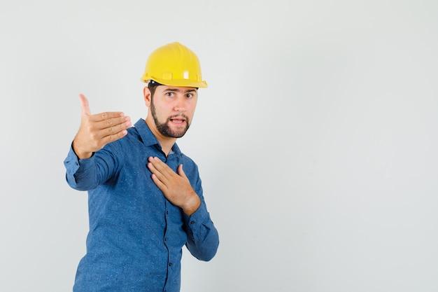 Jonge werknemer die uitnodigt om te komen, hand op borst in overhemd, helm houdt Gratis Foto