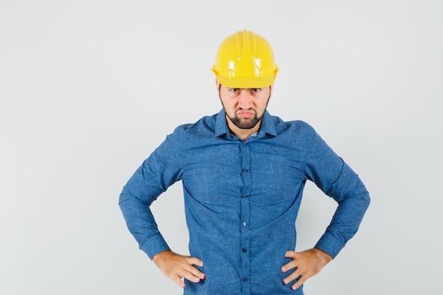Jonge werknemer hand in hand op taille in shirt, helm en woedend op zoek Gratis Foto