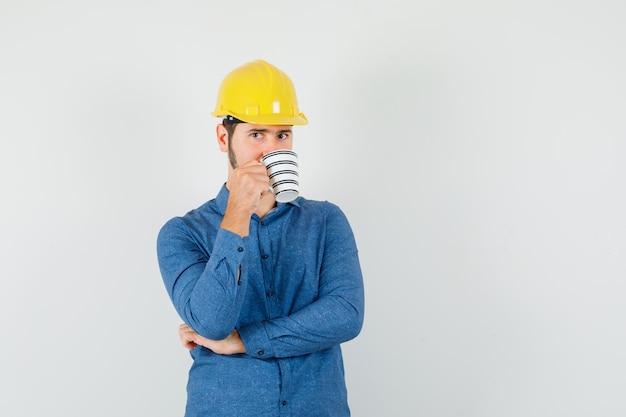 Jonge werknemer koffie drinken tijdens het denken in shirt, helm Gratis Foto