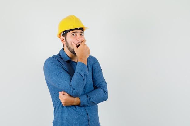 Jonge werknemer met hand op open mond in shirt, helm en verbaasd kijken Gratis Foto