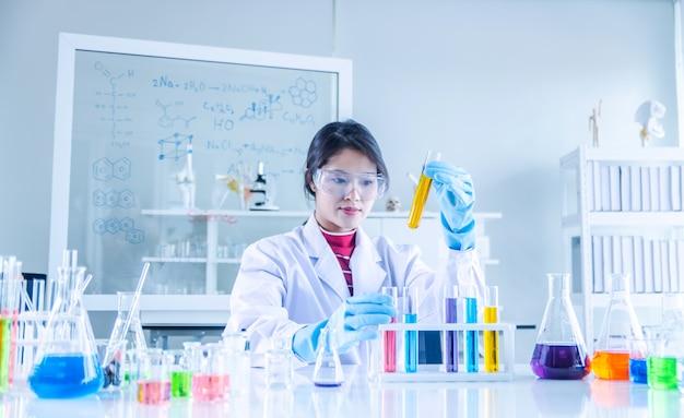 Jonge wetenschapper die door een buis in een laboratorium kijkt Premium Foto
