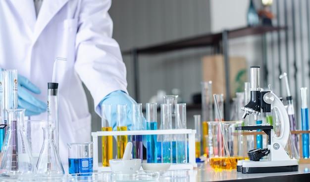 Jonge wetenschapper die door een microscoop in een laboratorium kijkt. Premium Foto