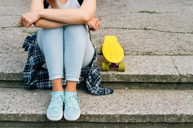 Jonge woaman in jeans, sneakers en t-shirt zittend op de stappen naast haar gele skateboard buitenshuis Premium Foto