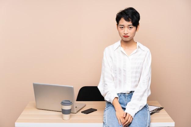 Jonge zakelijke aziatische vrouw op haar werkplek triest Premium Foto