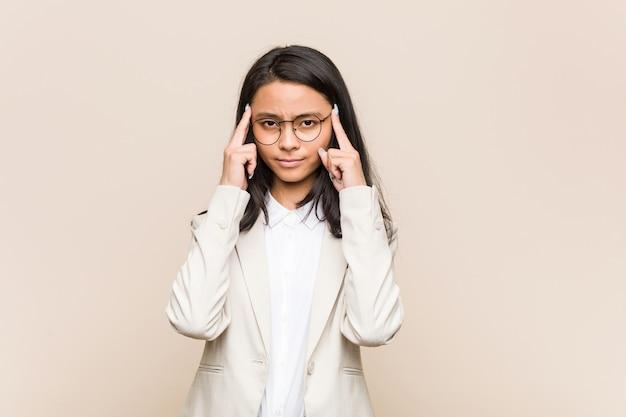 Jonge zakelijke chinese vrouw gericht op een taak, wijsvingers hoofd houden. Premium Foto