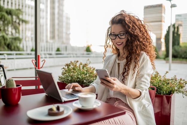 Jonge zakelijke roodharige vrouw op de computer en mobiele telefoon Premium Foto