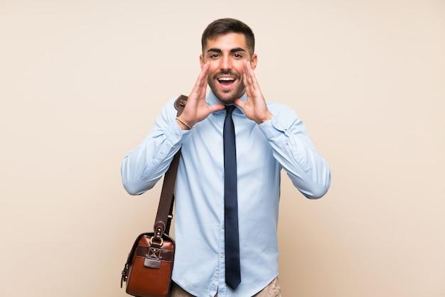 Jonge zaken met baard over geïsoleerde achtergrond die met wijd open mond schreeuwen Premium Foto