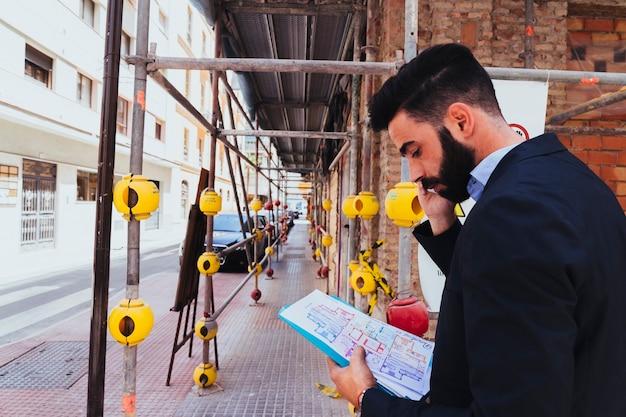 Jonge zakenman aan het werk en aan het praten over de telefoon Gratis Foto