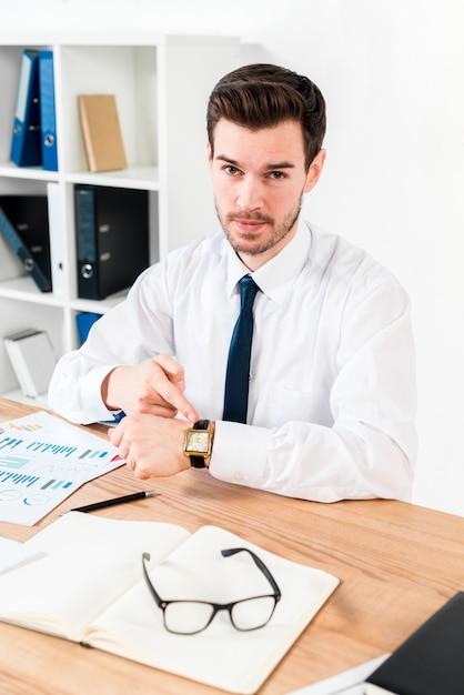 Jonge zakenman die aan camera kijkt die zijn vinger richt naar horloge op het werk Gratis Foto