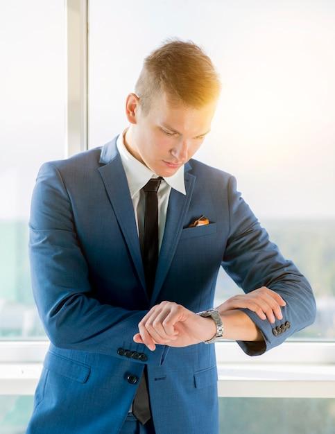 Jonge zakenman die de tijd controleert op polshorloge Gratis Foto