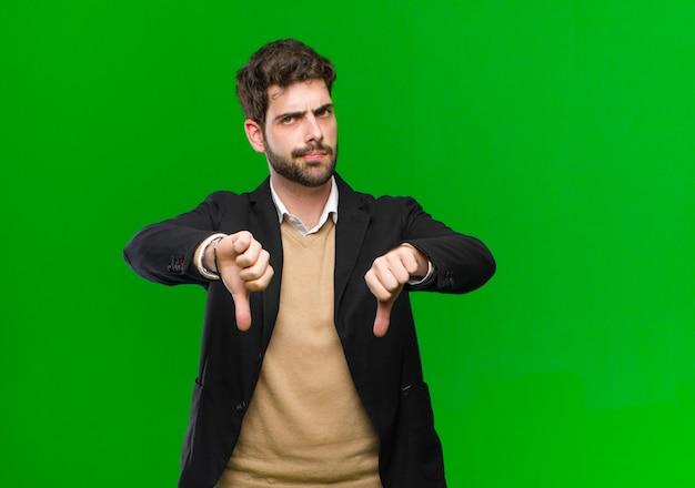 Jonge zakenman die droevig, teleurgesteld of boos kijken, die duimen neer in meningsverschil tonen, gefrustreerd voelen tegen groen Premium Foto