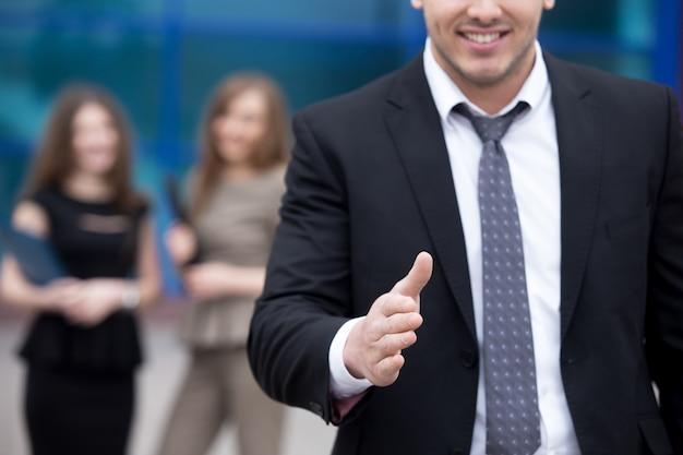 Jonge zakenman die hand voor handdruk aanbiedt Gratis Foto