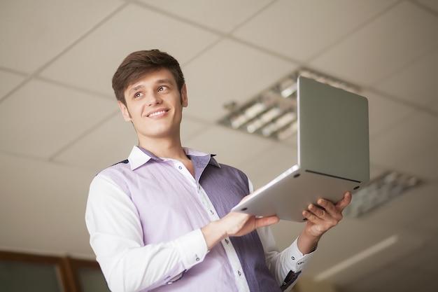 Jonge zakenman die laptop met behulp van terwijl status op het kantoor Premium Foto