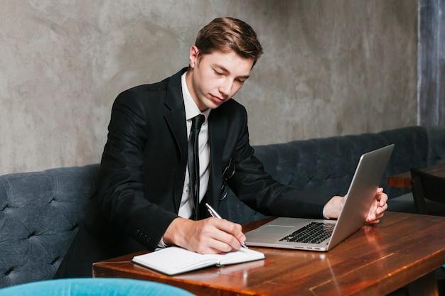 Jonge zakenman die met laptop werkt Gratis Foto