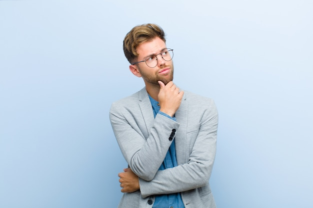 Jonge zakenman die, twijfelachtig en verward, met verschillende opties denken, benieuwd zijn welk besluit om tegen blauw te nemen Premium Foto