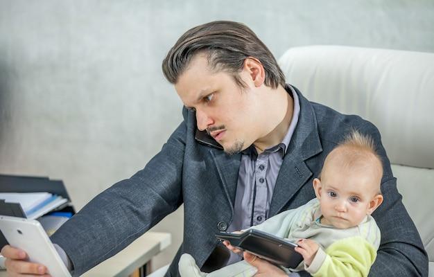 Jonge zakenman die vanuit zijn kantoor werkt en een baby vasthoudt Gratis Foto