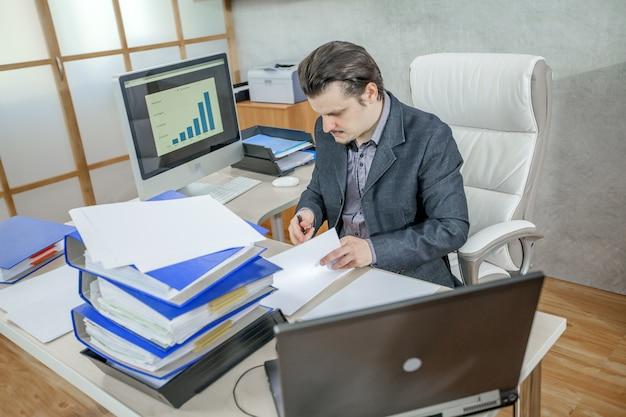 Jonge zakenman die vanuit zijn kantoor werkt - het concept van hard werken Gratis Foto