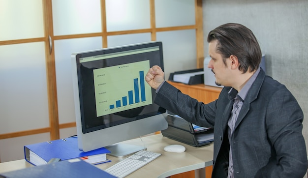 Jonge zakenman die vanuit zijn kantoor werkt - het concept van succes Gratis Foto