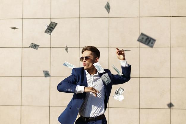 Jonge zakenman doorloopt rond dollars en danst op straat Gratis Foto