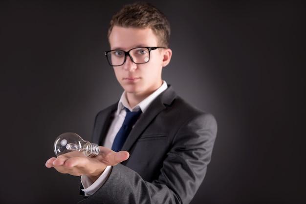 Jonge zakenman met gloeilamp in ideeconcept Premium Foto