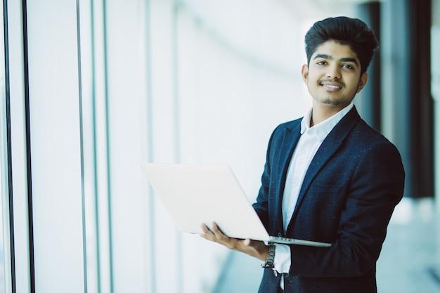 Jonge zakenman met laptop computer die op kantoor werkt Gratis Foto