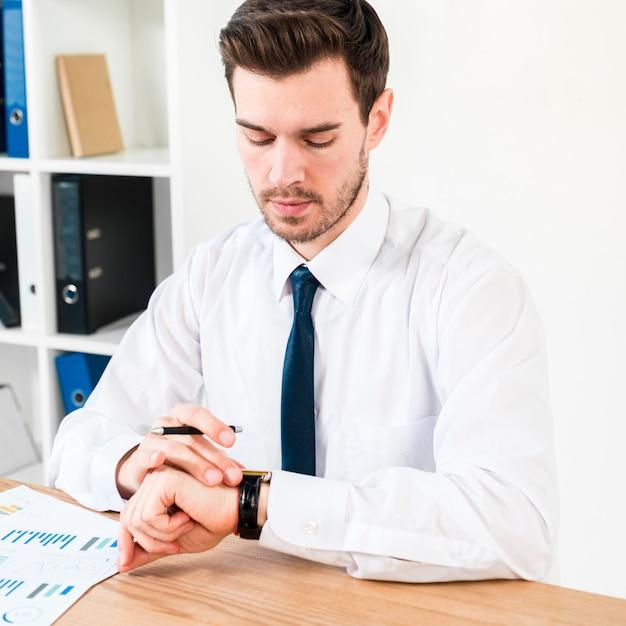 Jonge zakenman met pen in de hand kijken naar de tijd op polshorloge Gratis Foto
