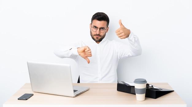 Jonge zakenman op een werkplek die goed-slecht teken maakt. onbeslist tussen ja of niet Premium Foto