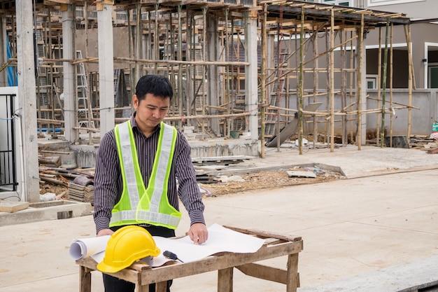 Jonge zakenman professionele ingenieur werknemer op de bouwplaats huis bouwen met blauwdruk Premium Foto