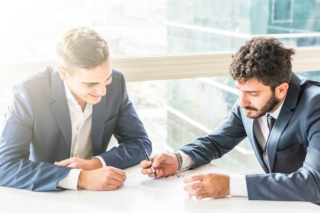 Jonge zakenman twee die het businessplan op wit bureau plant Gratis Foto