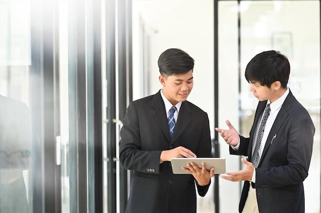 Jonge zakenman twee raadpleegt en ontmoet bedrijfsbespreking. Premium Foto