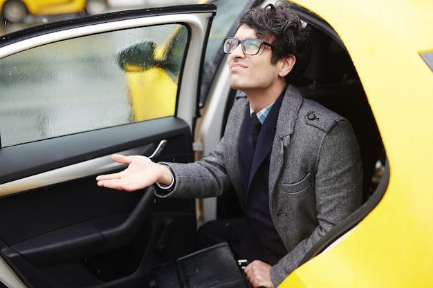 Jonge zakenman verlaten taxi in regen Gratis Foto