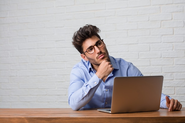 Jonge zakenman zitten en werken aan een laptop te denken en op te kijken Premium Foto