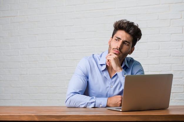 Jonge zakenman zitten en werken aan een laptop twijfelen en verward Premium Foto