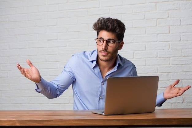 Jonge zakenman zitten en werken op een laptop twijfelen en schouders ophalen, concept van besluiteloosheid en onzekerheid, onzeker over iets Premium Foto