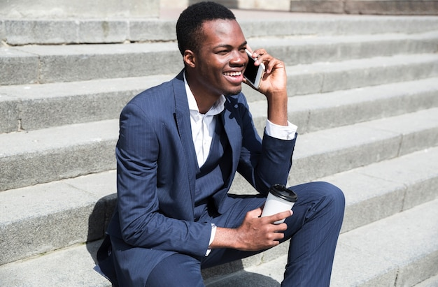 Jonge zakenman zittend op stappen bedrijf wegwerp beker in de hand Gratis Foto