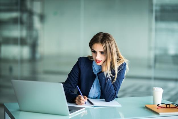 Jonge zakenvrouw in glazen zittend op houten tafel met laptop, plant, wegwerp kopje koffie en schrijven op het papier, met een pen en smartphone Gratis Foto