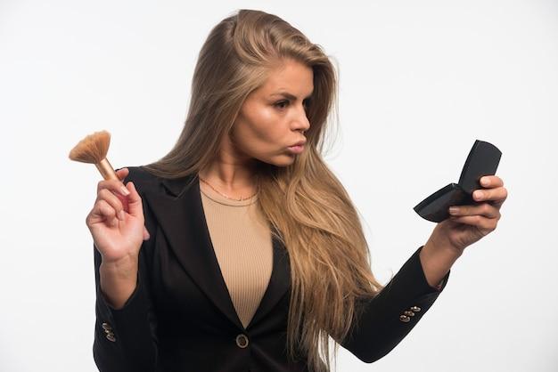 Jonge zakenvrouw in zwart pak make-up toe te passen en op zoek naar de spiegel. Gratis Foto
