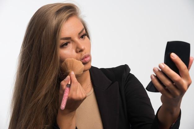 Jonge zakenvrouw in zwart pak make-up toe te passen op haar wang. Gratis Foto