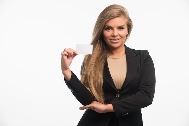 Jonge zakenvrouw in zwart pak visitekaartje van de klant controleren en glimlachen. Gratis Foto